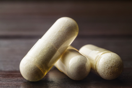 White capsules of glucosamine chondroitin, healthy supplement pills on wooden table, macro image. Stock Photo
