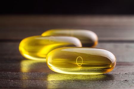 Yellow capsules omega 3, fatty acid, fish oil on dark wooden table, macro image. Stock fotó - 91174409