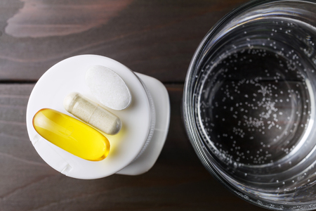 Complex of vitamins and dietary supplement, yellow capsule of omega 3, white capsule of glucosamine, calcium pill on the white plastic bottle and glass of water at wooden table, top view. Stock Photo