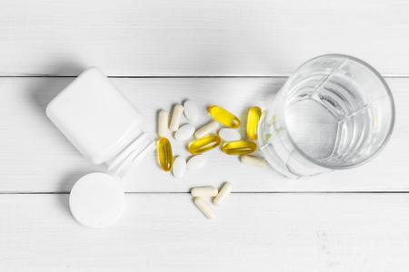 Gele capsules omega 3, witte pillen van calcium, glucosaminesupplementen, glas water en plastic fles op houten plankenlijst, hoogste mening.