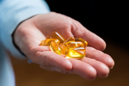 Yellow medication capsules of omega 3, fish oil, healthy supplement pills in the woman palm hand. Stock Photo