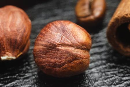 Brown, raw hazelnut kernel on black leather texture background, macro image. Stock Photo
