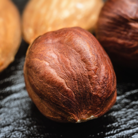Brown, raw hazelnut kernel and almond nuts on black leather texture background, macro image.