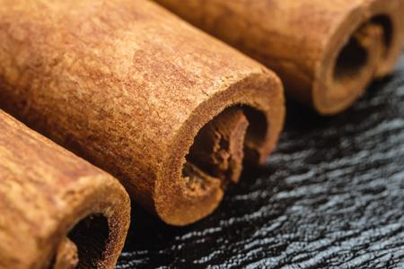 Cinnamon stick on black leather texture background, macro image. Stock Photo