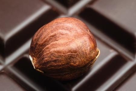 One brown kernel of raw hazelnut on dark bitter chocolate bar, macro image. Stock Photo