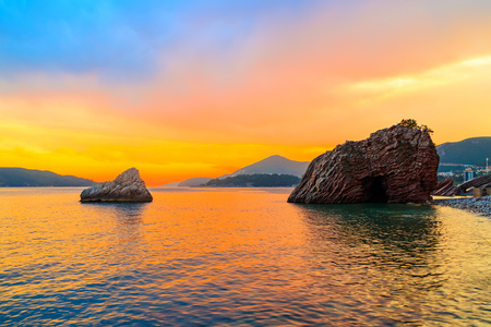 Awesome colorful sunset on the Adriatic sea near Budva city in Montenegro, gorgeous seascape with big rock in the beach.