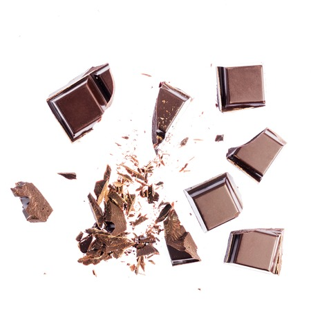 Chocolate cubes, pieces of bitter, dark chocolate, isolated on white background, top view.