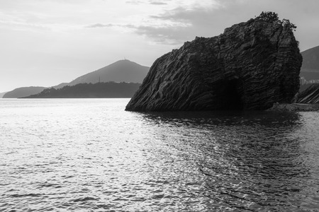 Adriatic sea with rock in the water at Montenegro, black and white.