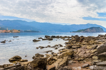 Mogren beach with big stones, old city Budva and Sveti Nikola island at Adriatic sea coastline in Montenegro.