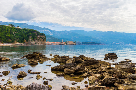 Mogren beach with big stones and old city Budva at Adriatic sea coastline in Montenegro, summer seascape.