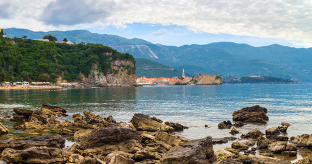 Mogren beach with big stones and old city Budva at Adriatic sea coastline in Montenegro, summer seascape, panoramic view.