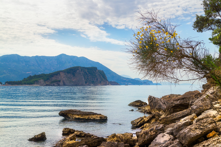 Mogren beach with big stones and Sveti Nikola island at Adriatic sea coastline in Montenegro. Stock Photo