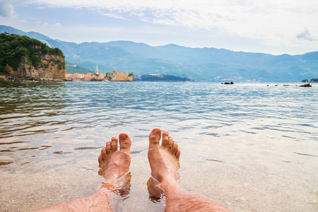 Two hairy man legs in the transparent Adriatic sea water on Mogren beach, view to the old city Budva.