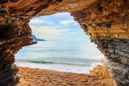View from the cave in cliff to the blue Adriatic sea in Montenegro near Budva city, summer seascape.