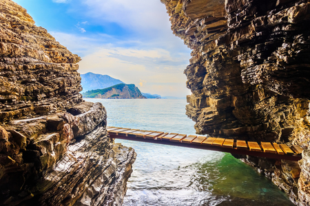 Bridge between two cliffs on the Adriatic sea coastline near Budva city at Montenegro, summer seascape.