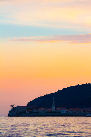 Awesome sunset on Adriatic sea coastline, view to the Budva city at Montenegro.