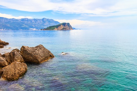 Adriatic sea coastline, Sveti Nikola island and big stones on foreground, Montenegro, summer seascape. Stock Photo