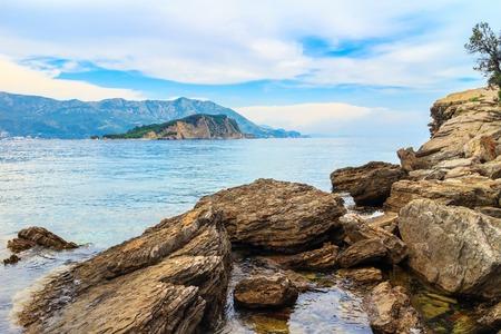 Mogren beach with big stones and Sveti Nikola island at Adriatic sea coastline in Montenegro. 스톡 콘텐츠