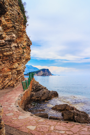 Adriatic sea coastline with rocks in Budva city, view to the Sveti Nikola island, Montenegro, summer seascape.