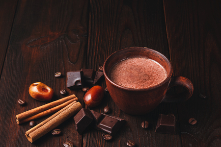 Hot chocolate drink in a brown clay cup, chocolate cubes, cinnamon sticks and coffee bean on the dark wooden background.