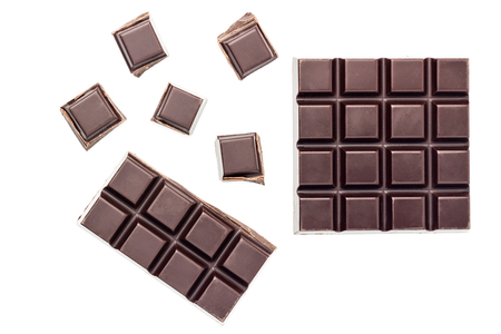 Chopped chocolate cubes, bitter, dark chocolate bar isolated on white background, top view.