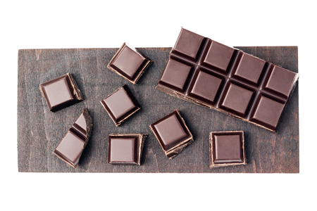 Chopped chocolate cubes, pieces of dark chocolate bar on a brown plank, isolated on white background, top view.