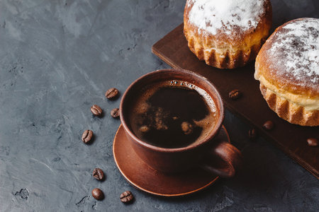 Coffee cup and muffins on the dark, textured background.