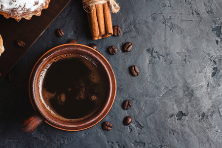 Cup with hot coffee, muffins and cinnamon sticks on the dark, textured background, top view. Stock Photo