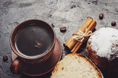 Cup with hot coffee, muffins and cinnamon sticks on the dark, textured background.