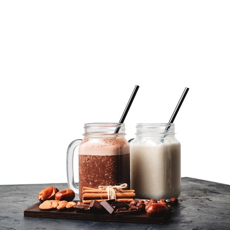 Banana and chocolate smoothie in two jars, protein milkshake, nuts, chocolate cubes, dates, cinnamon sticks on a dark table isolated on white background.