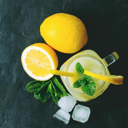 Refreshing lemonade drink with lemon slice and mint in the jar on dark background, top view.