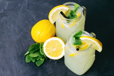 Refreshing lemonade drink with lemon slice and mint in the jar on dark background. Stock Photo