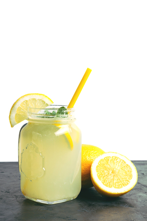 Refreshing lemonade drink with lemon slice and mint in the jar on dark table and white background.