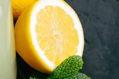 Lemon halves and mint on a dark background.