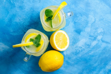 Refreshing lemonade drink with lemon slice and mint in the jar on a blue background, top view. Stock Photo