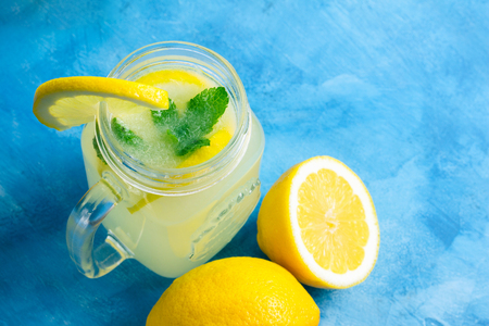 Refreshing lemonade drink with lemon slice and mint in the jar on a blue background.