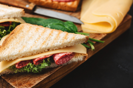 Sandwiches on a cooking board, grilled toast, salami sausage, salad lettuce and cheese on a dark background.