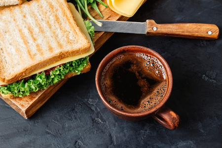 Cup with hot coffee and sandwich with grilled toast, salami sausage, salad lettuce and cheese on dark background.