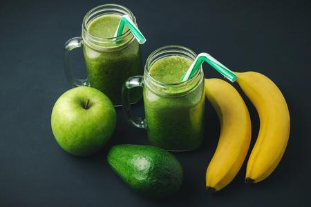 Green, healthy, detox smoothie from avocado, banana, apple in mason jar on dark background, vegetarian food.