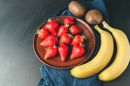 Red strawberry in the plate, banana and kiwi fruit on dark background with blue napkin.