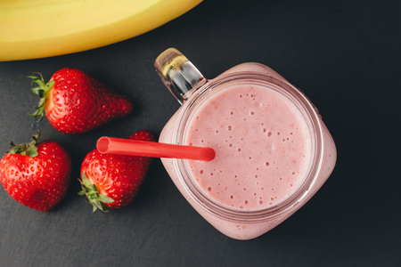 Smoothie with strawberry and banana in the jar at dark background, top view.