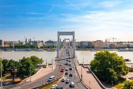 View to the Pest side of Budapest city in Hungary and bridge over Danube river with boats .