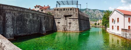 Emerald green water and ancient stone city wall of Kotor old town former Venetian fortress in Montenegro.