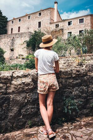 Rear view of young woman who looking to the ancient stone building in Budva city, Montenegro. Stockfoto