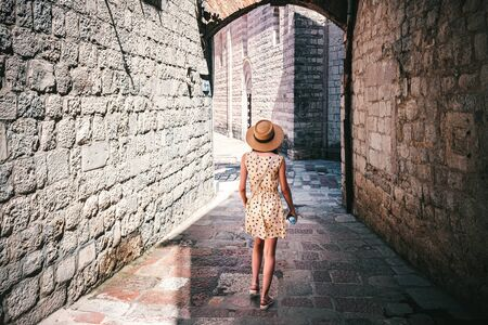 Rear view of young woman in dress and hat, walking on the narrow street in the medieval city Kotor, Montenegro.