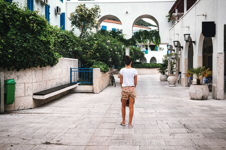 Rear view of young woman walking on the street with white houses and blue shutters in Budva city, Montenegro. Stockfoto