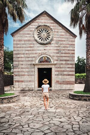 Rear view of young woman standing before church in Podmaine or Podostrog orthodox Monastery, Montenegro.