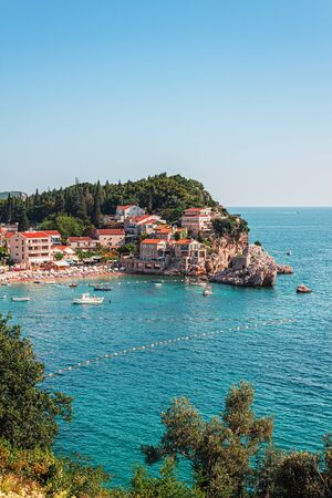 Picturesque summer view of Adriatic sea coast in Budva Riviera. Przno village with buildings on the rock, Montenegro.
