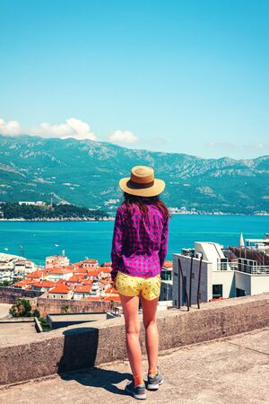 Rear view of young woman in hat, who looking to the Budva city from above, Montenegro.
