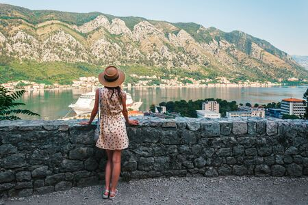 Rear view of young woman in dress and hat, who looking from above to the Kotor city and Boka bay, Montenegro.